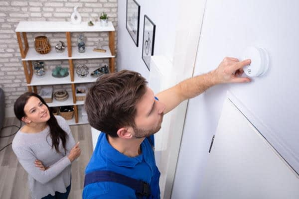 domestic electrician testing wall-mounted smoke detector while smiling woman watches