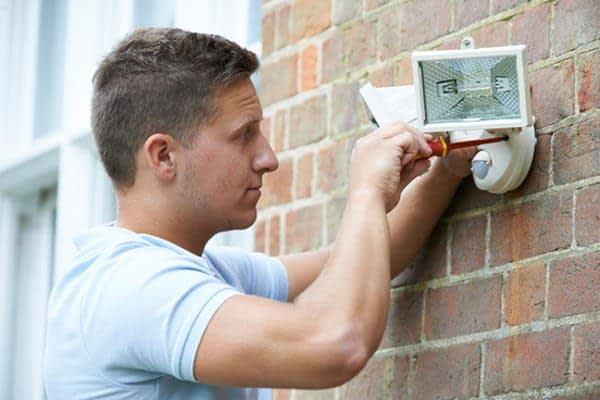 electrician conducting security lighting installation outside