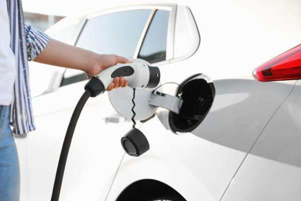woman plugging EV charging point into parked car