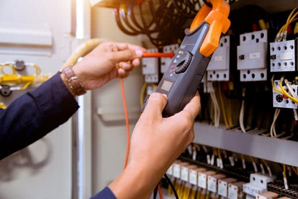 domestic electrician measuring the electrical safety of control panel
