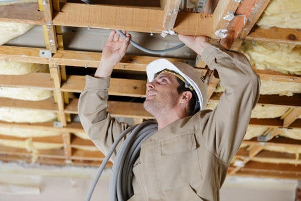 domestic electrician conducting rewire inside ceiling